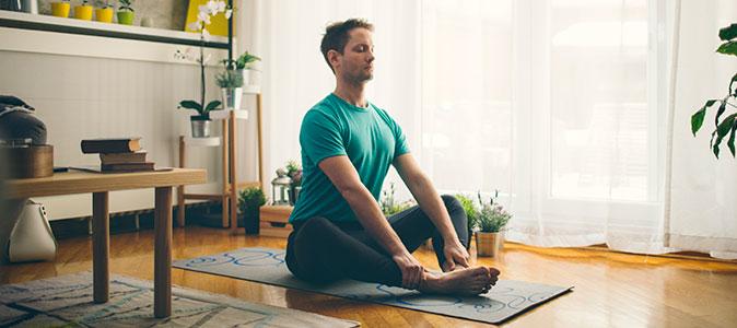 homem medita em uma sala de estar