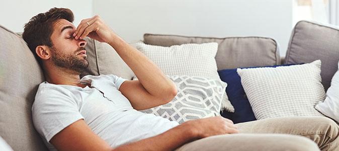 rapaz sentado no sofá cm dores de cabeço