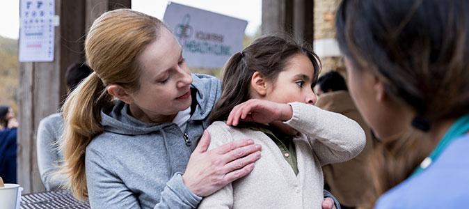 criança no colo da mãe. A criança tosse e cobre sua boca e nariz com o braço.