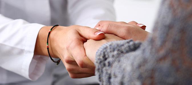 Mãos de uma médica segura as mãos de uma paciente