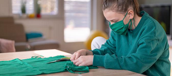 uma garota faz máscaras de tecido