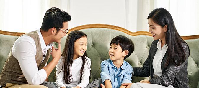 família asiática conversa na sala