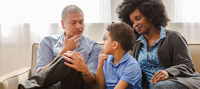 pais conversam com o filho na sala