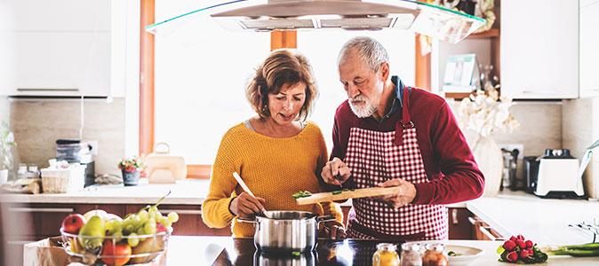 casal idoso cozinhando juntos