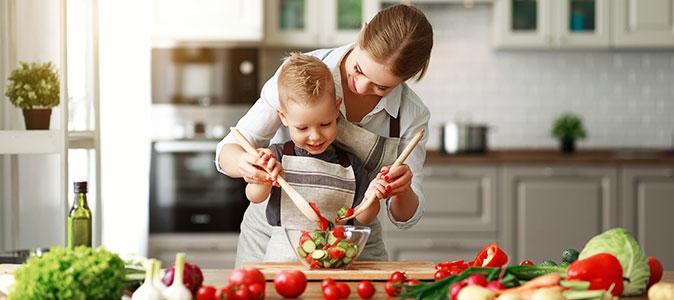 mãe e filho preparando uma salada