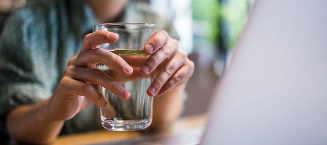 uma mulher segura um copo com água na frente de um notebook