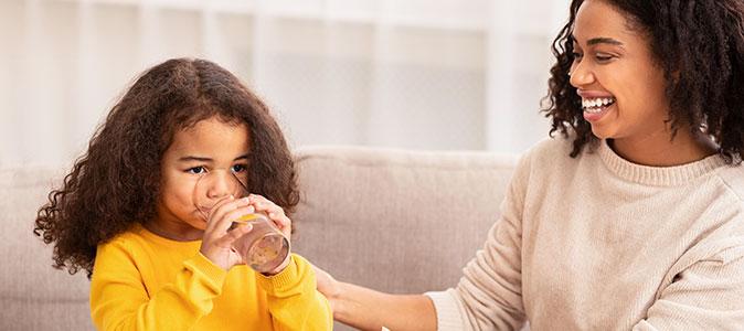 mãe dar um copo de água para sua filha