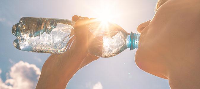 uma mulher bebe água em uma garrafa ao ar livre