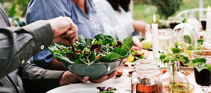 salada de folhosos sendo posta na mesa
