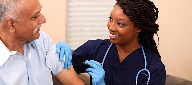 Uma enfermeira aplica uma vacina em um senhor idoso