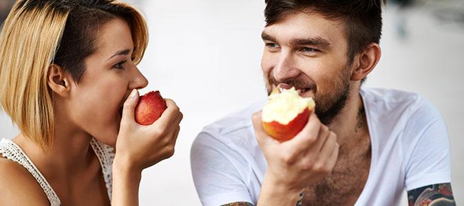 um casal come maçãs