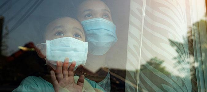 mãe e filha atrás do vidro de uma janela usam máscaras