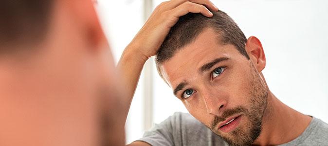 rapaz passa a mão no cabelo em frente ao espelho