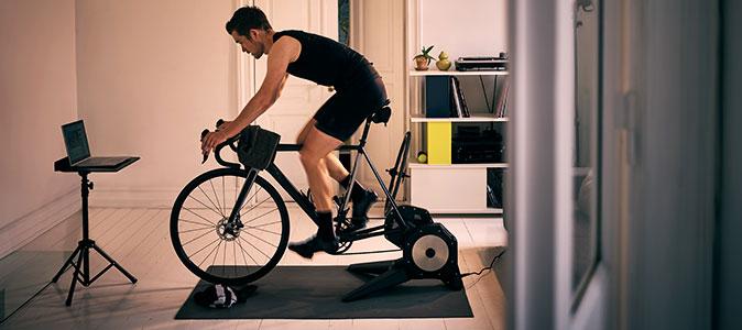 Homem treina ciclismo indoor na sala