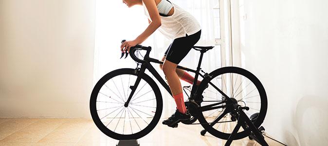 Mulher treina ciclismo indoor na sala de casa