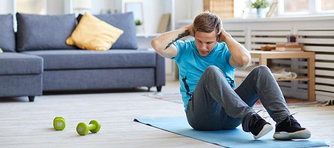 rapaz realiza exercícios na sala de casa