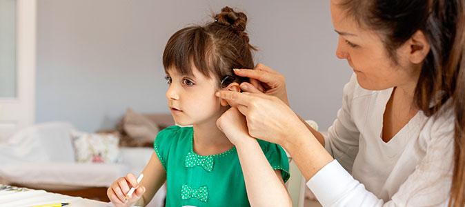 mãe ajuda filha a inserir o aparelho auditivo