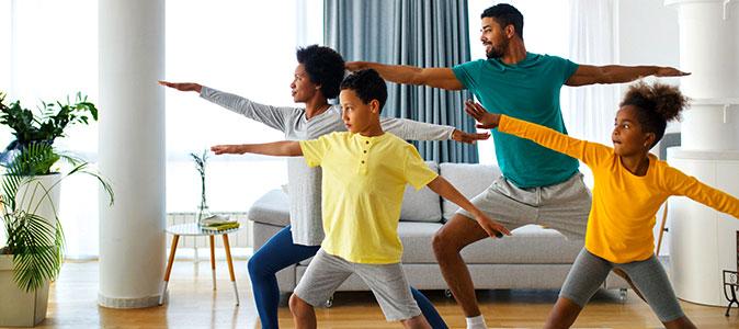 pais e filhos fazem ioga em casa