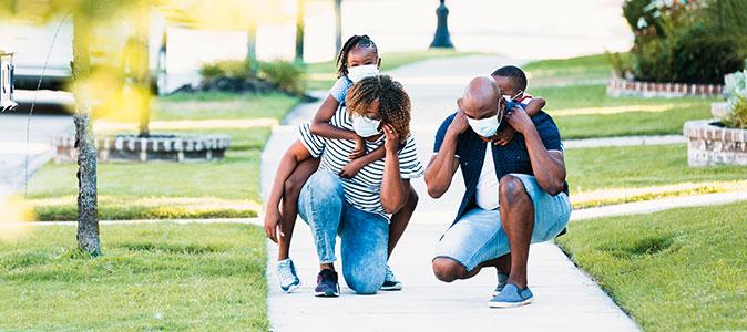 família caminha na rua com os filhos