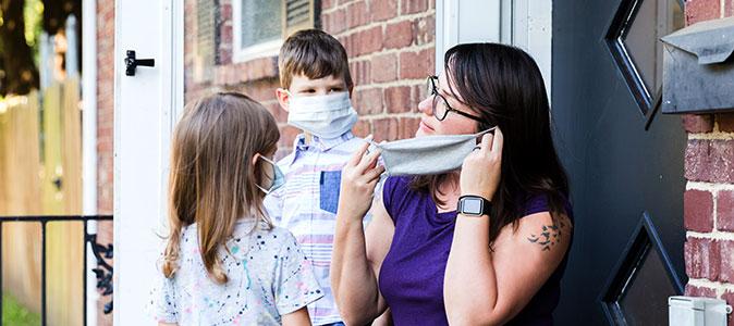 mãe coloca máscaras nos filhos