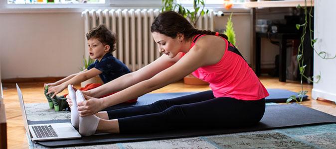 mãe e filho se exercitam na sala de casa