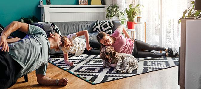 família se exercita na sala de casa