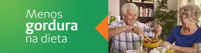 Menos gordura na dieta. Casal de idosos sentados à mesa e comendo uma salada.