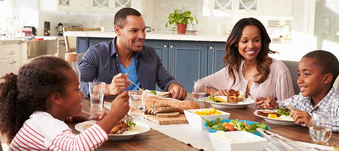 família almoçando em uma mesa na cozinha