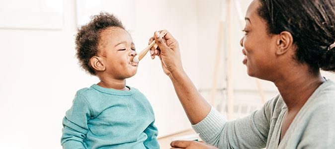 mãe dando iogurte para seu filho bebê