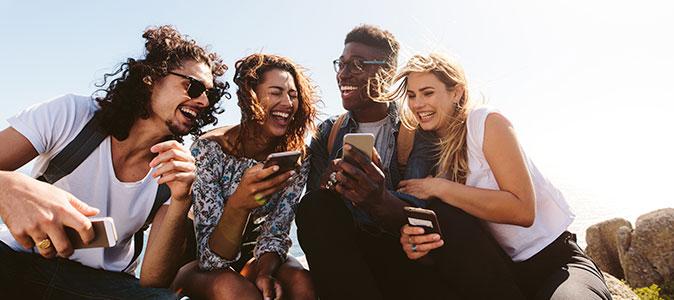grupo de amigos utilizando smartphones e rindo