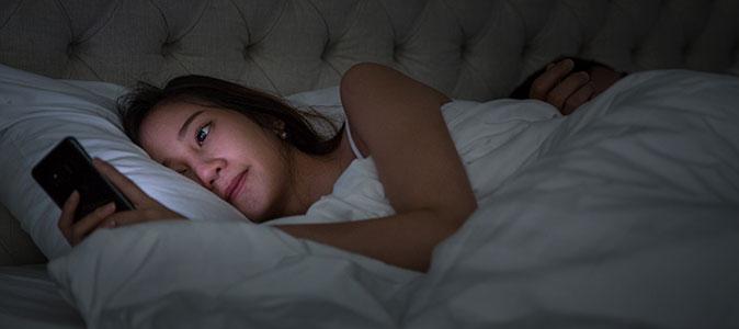 mulher deitada e utilizando um smartphone