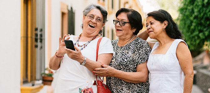 senhoras amigas rindo e utilizando um celular