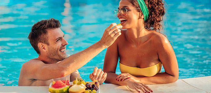 casal comendo frutas na piscina