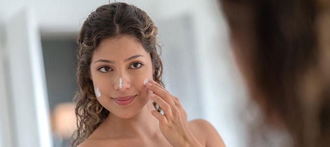 mulher passando protetor solar no rosto