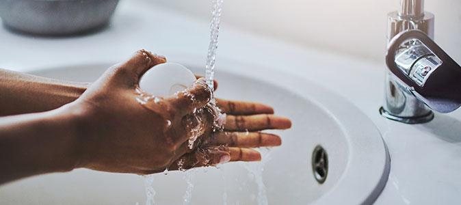 alguém limpando as mãos com sabão em uma pia