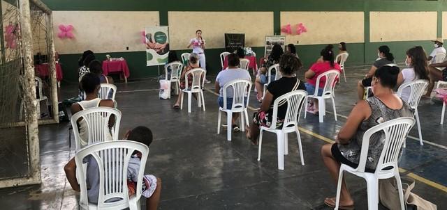 A foto mostra uma mulher na frente de grupo de pessoas.